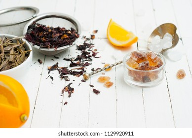 green and black herbal tea crop variation with lemon, rock sugar and infuser, on white wooden table background