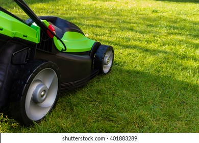 green black lawn mowers at garden with green grass