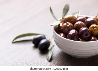 Green and black marinated olives and oil on gray background copy space