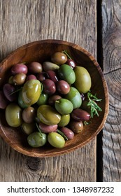 Green and black olives with olive oil and rosemary