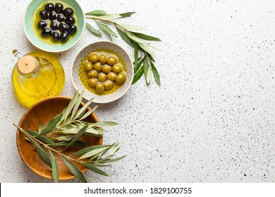 Green and black olives with olive oil in a glass bottle, olive tree sprigs and cut fresh ciabatta bread on wooden cutting board. White rustic background, healthy mediterranean food, space for text