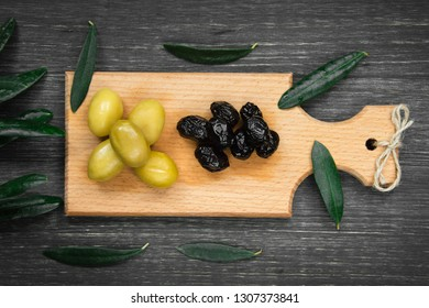 Green and black olives on the wooden plate with olive-tree leaves on black background.