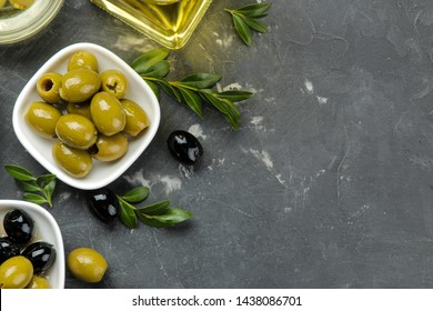 Green and black olives in a white ceramic bowl with leaves on a dark graphite background. top view. space for text