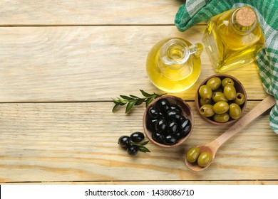 Green and black olives in a wooden bowl with leaves and olive oil on a natural wooden table. top view.