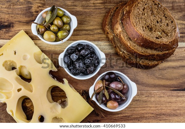 Green, black, pink olives in white porcelain bowls, piece of cheese and bread slices on a wooden board.