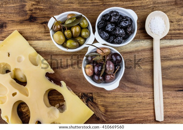 Green, black, pink olives in white porcelain bowls, piece of cheese and a wooden spoon.