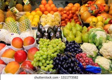 Green black red berries of grapes, mango, pears, apples, pineapple, melon are on the market for sale
