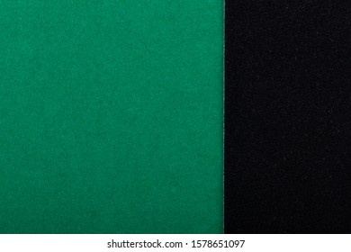 Green and black sheets of colored velvet paper. Bright color dark background. Horizontal orientation. Square and vertical strip. Top view flat lay with copy space.