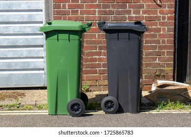 a green and a black wheelie bin side by side on a street