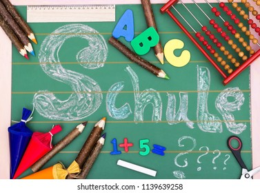 A green blackboard with letters, numbers and crayons