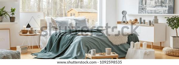 スカンジナビア風の寝室の内側に広い窓があり、森を見渡せる、居心地の良い二重ベッドの上に緑の毛布