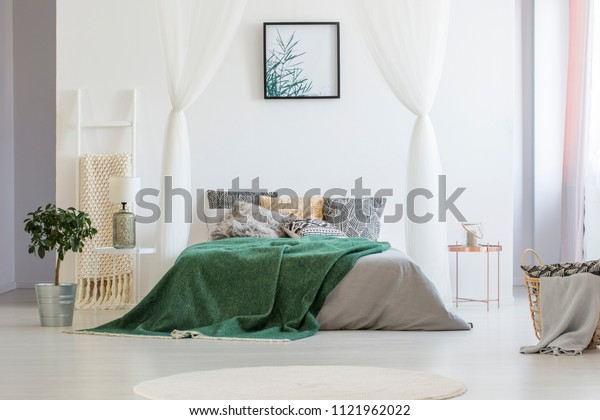 Green blanket thrown on double bed with many pillows and grey sheets standing in white hotel room interior with simple poster on the wall, plant on the floor and glass lamp on bedside table