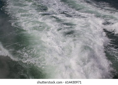 Green blue foaming water wake behind boat.