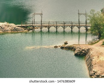 Green blue lake with wooden tourist path bridge above cold water. Hiking in the national park