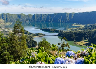 Green and blue lakes seen from above, with a blue sky and lush vegetation around. They are the Lagoa Verde and Lagoa Azul, also known as Lagoa das Sete Cidades, on Sao Miguel in the Azores islands.
