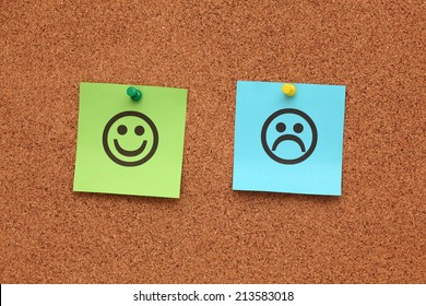 Green and blue paper with happy and sad faces on corkboard (bulletin board).