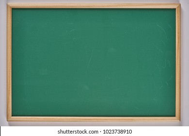 Green board with wooden frame for background.