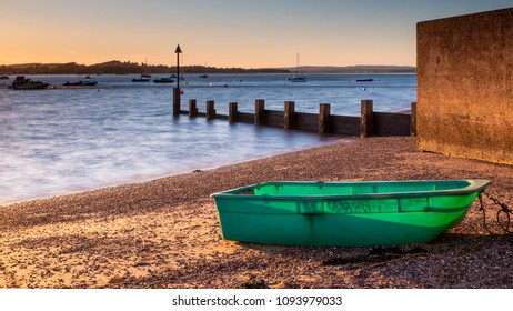 Green boat on Exmouth beach at sunset