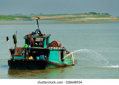 Green boat on Irrawaddy river close to Mandalay Burma Myanmar