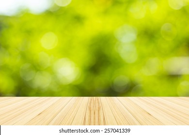 Green bokeh and sunlight with wood terrace.