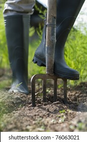 Green boots digging the garden with fork close up