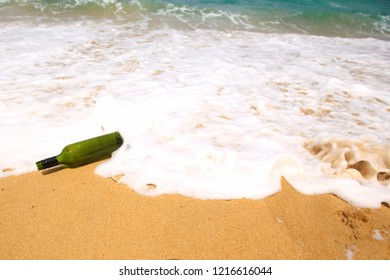 Green bottle at the beach