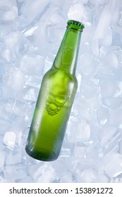 A green bottle of beer on ice.