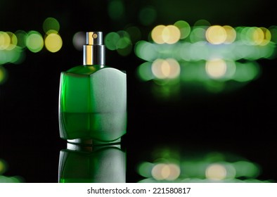 Green bottle with perfume on a black background