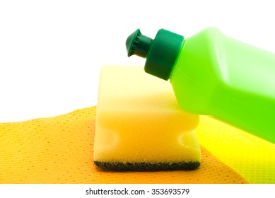 green bottle, rags and yellow sponge on white background