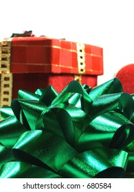 green bow, with box and red ribbon. focus on green bow in front.