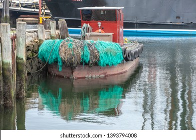 Green bow pudding on water tender reflecting off calm water in New England harbor