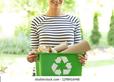 Green box with a recycling sign filled with paper held by a smiling woman