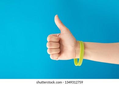 Green bracelet on female girl hand on blue background. Green concept and vote for nature. Music festival branding empty wristband.