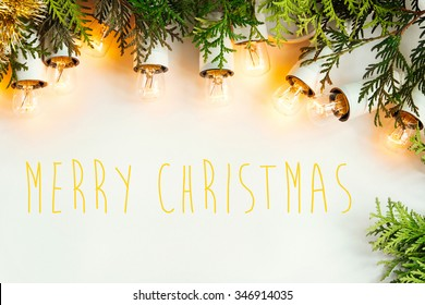 green branches of cedar and amazing beautiful christmas vintage garland lights on white background, merry christmas text