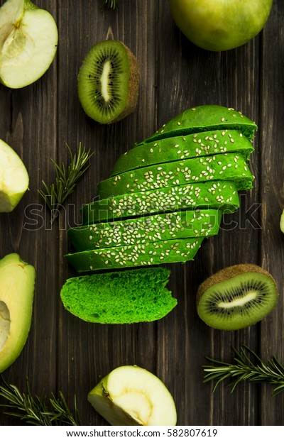 green bread with sesame seeds - close to green fruit. avocado, apple, kiwi and rosemary
