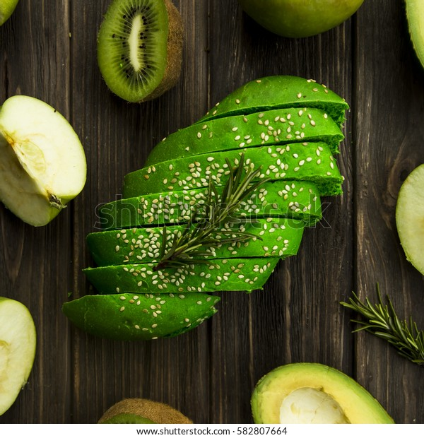 green bread with sesame seeds - close to green fruit. avocado, apple, kiwi and rosemary. top view