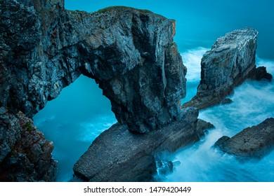 Green Bridge of Wales, famous rock formation and iconic landmark on Pembrokeshire coast, South Wales, Uk, photographed during blue hour.Long exposure image.Coastline scenics.Twilight nature.Seascape.