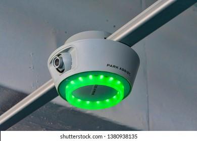 Green bright LED light on smart-sensor by Park Assist signal parking guidance to drivers to open spots at Santana Row parking garage  - San Jose, California, USA - April 23, 2019