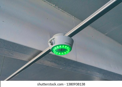Green bright LED light on smart-sensor by Park Assist signal parking guidance to drivers to open spots at Santana Row parking garage  - San Jose, California, USA - April 23, 2019