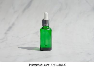 Huile essentielle au visage de bouteille verte et brune ou emballage en sérum sur fond marbré blanc. Produit cosmétique de beauté pour le concept de soins de la peau. style minimaliste et luxueux. Lumière et ombre.