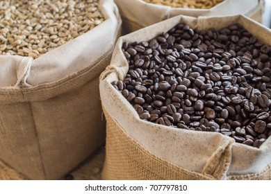 Green and brown coffee bean unroasted and black roasted coffee beans in sack
