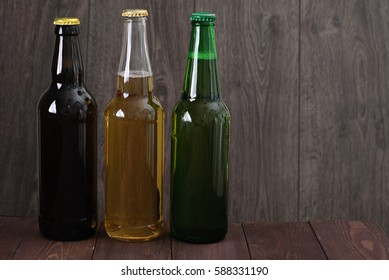 Green and brown glass bottles of beer on table over wooden background, close up
