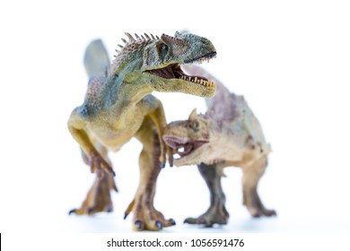 Green and brown Long Running Carnotaurus biting an Allosaurus - focus on the Allosaurus