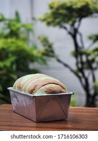 Green and brown swirl bread loaf dough in tin mold on wooden table with garden background.