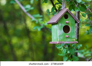 Green and brown wooden birdhouse hanging from tree with foliage blurred in background