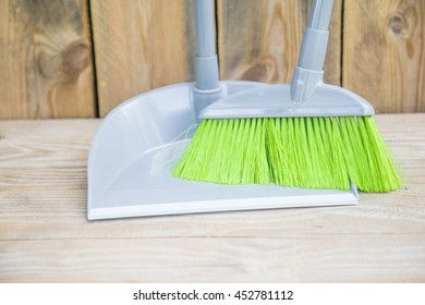 Green brush sweep with dustpan for house work on wooden floor outdoors.Cleaning and home idea related concept.