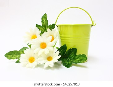 Green bucket decorated with white flowers and leaves on white background