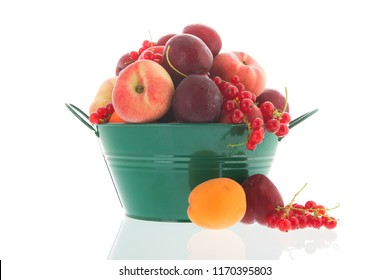 Green bucket full with fresh summer fruit isolated over white background