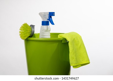 Green bucket with spray bottle, green cloth and green dishwashing brush.