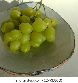 Green bunch of grapes on a rustic plate